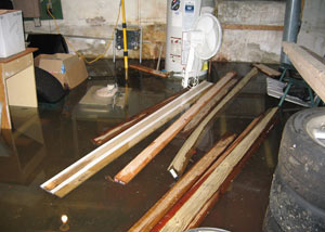 A severely flooding basement in Newfield, with lumber and personal items floating in a foot of water